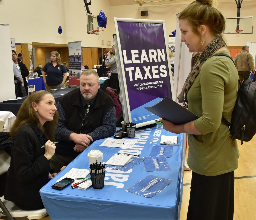 Cristine Aston, left, and Don Hart, of Jackson Hewitt Tax Service, answer questions Thursday from Karina Beadling during a job fair held at Kennebec Valley Community College's Hinckley campus.