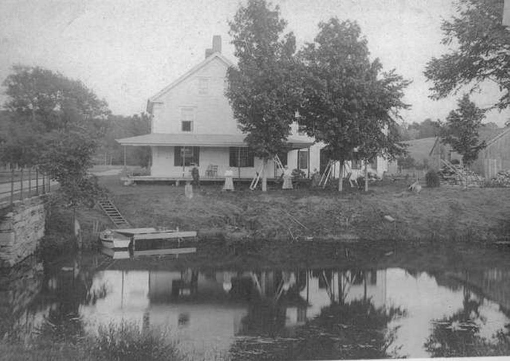 Summer visitors enjoy leisure time at the Meserve House by the Bridge on Davis Stream. The photo is one of 40 photos featured in the 2019 version of the JHS's 2019 calendar.