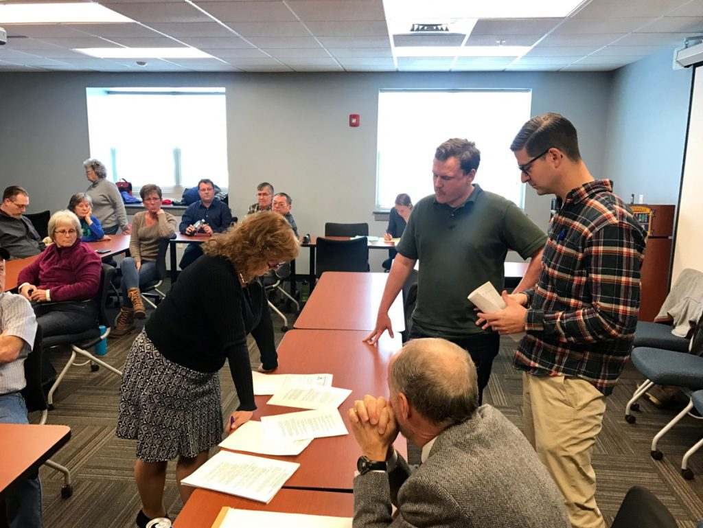 Waterville City Clerk Patti Dubois, left, presents disputed ballots to Todd Martin, of the Sustain Mid-Maine Coalition, right center; Waterville Mayor Nick Isgro, far right; and City Attorney Bill Lee, seated, after the recount of votes on the referendum on plastic shopping bags.