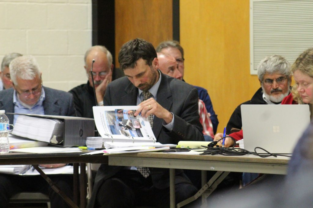 Attorney David Kallin, center, reviews evidence at Thursday night's public hearing on a proposed expansion of Mere Point Oyster Co.'s cultivation operation in Brunswick. Kallin is representing the Maquoit Bay Preservation Group, or the Concerned Citizens of Maquoit Bay.