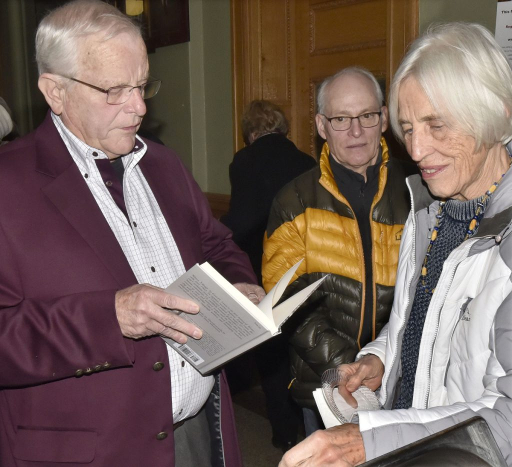 "Earl Smith signs his book ""Water Village, The Story of Waterville, Maine,"" for Louise Smith during a reception Thursday in the Waterville City Hall lobby. ""I've read all of his books,"" Louise Smith said. Steve Collins is at center."