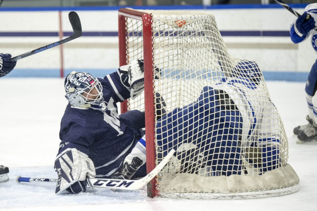 Colby College's Brendan Murphy (12) ends up in the goal on top of Middlebury College goalie Brian Ketchabaw (30) at Alfond Rink in Waterville on Friday.