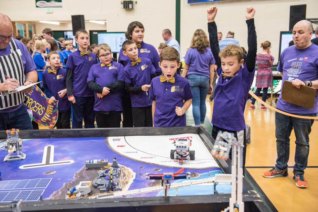 Jayce Thompson raises his hands in victory as his robot completes a task during the Western Maine FIRST Lego League Qualifier at Spruce Mountain High School in Jay on Saturday. Members of his team, The Enforcers, from RSU 16 in Poland react.