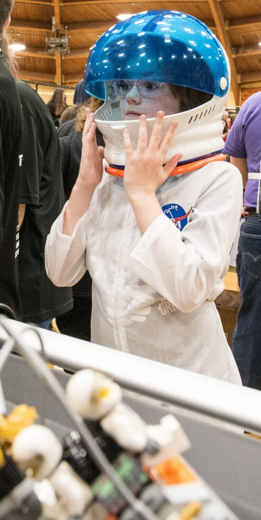 Melissa Finnemore raises the visor of her spacesuit to get a better look at the progress her team's robot was making during Saturday's competition at Spruce Mountain. She is a member of team StarFish from Fairfield.
