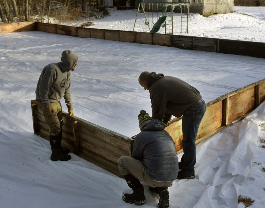 Trevor Knell, left, Ryan Cote, and Tom Langlois stake the boards of an ice rink Sunday in the back yard of Langlois' Monmouth home. The men's children play hockey together.