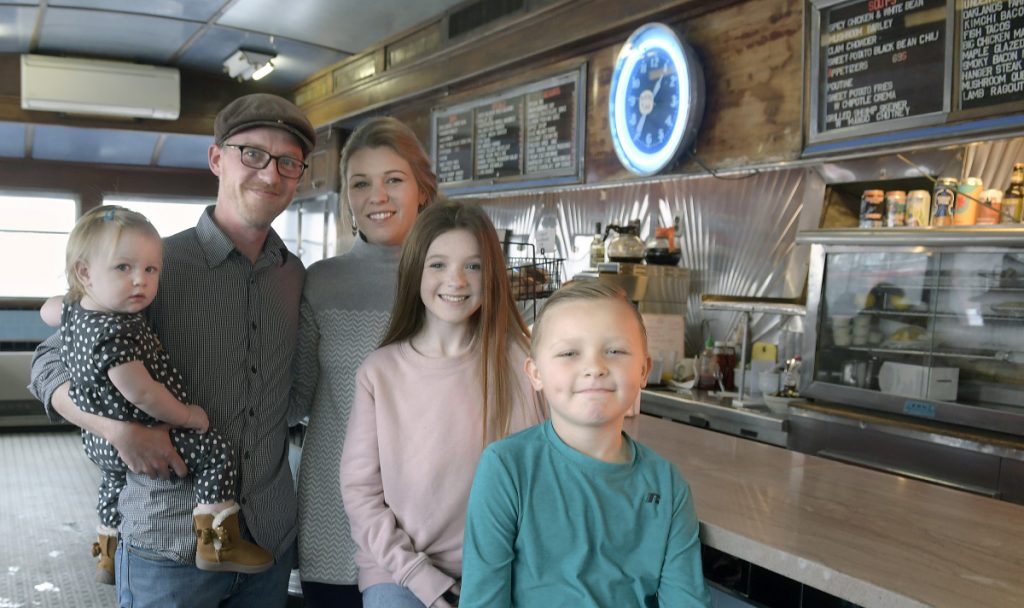 Aaron Harris with his wife, Sarah, and children Eleanor, 1, left, Spencer, 8, and Olivia, 11, at the A1 Diner in Gardiner. After three decades, Michael Giberson and Neil Andersen are handing the reins of the institution over to Aaron Harris. The family gathered on Monday at the Diner.