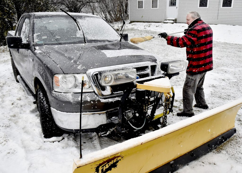 Peter Webb brushes snow off his plow truck as snow falls Tuesday in Skowhegan.
