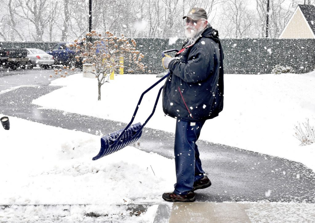 City of Waterville employee Bob LaPlante kicks sticky snow off his shovel while clearing sidewalks Tuesday at the Waterville police station.