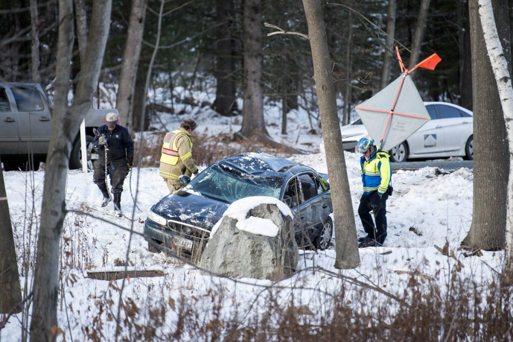 Waterville firefighter Lt. Scott Holst, of Engine 2, along with a Delta Ambulance emergency medical technician and a tow truck driver from Arbo's, tend to a car that went off the road Wednesday near exit 127 in the southbound lanes of Interstate 95 in Waterville.