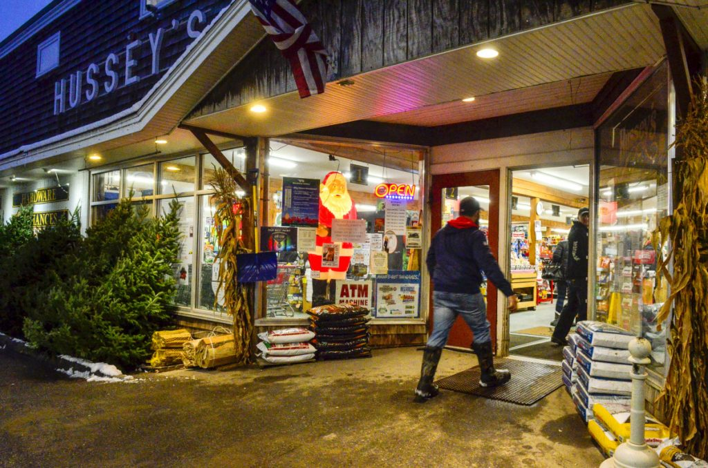 Shoppers walk past a glowing Santa Claus figure Wednesday as they enter Hussey's General Store in Windsor.