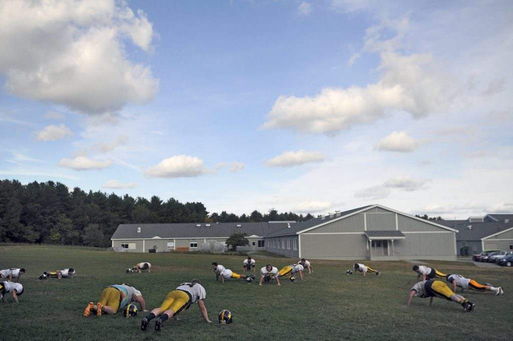 The Maranacook Community High School football squad does sit-ups in 2016 during practice at the Readfield school.