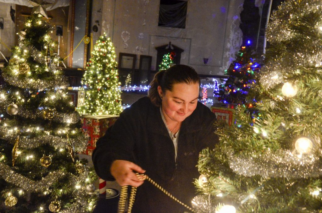 Kayla Guenard decorates the Capital City Coins tree Wednesday at the Colonial Theater in Augusta. The River of Trees event starts Friday and runs through Sunday.