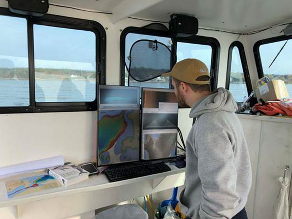 Ben Kraun monitors data from the multibeam echosounder system this year while out on the Amy Gale searching for the wreck of the Angel Gabriel in Bristol.