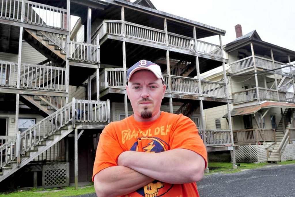 "Bobbi Frappier stands outside the Waterville apartment building known as the ""Beehive"" on June 25, 2013. Frappier was 12 years old when he found his grandmother Martha Daigle murdered in 1989 in the building. Alan Powell was convicted for the murder and died at the Maine State Prison after an altercation with convicted murderer Guy Hunnewell lll."