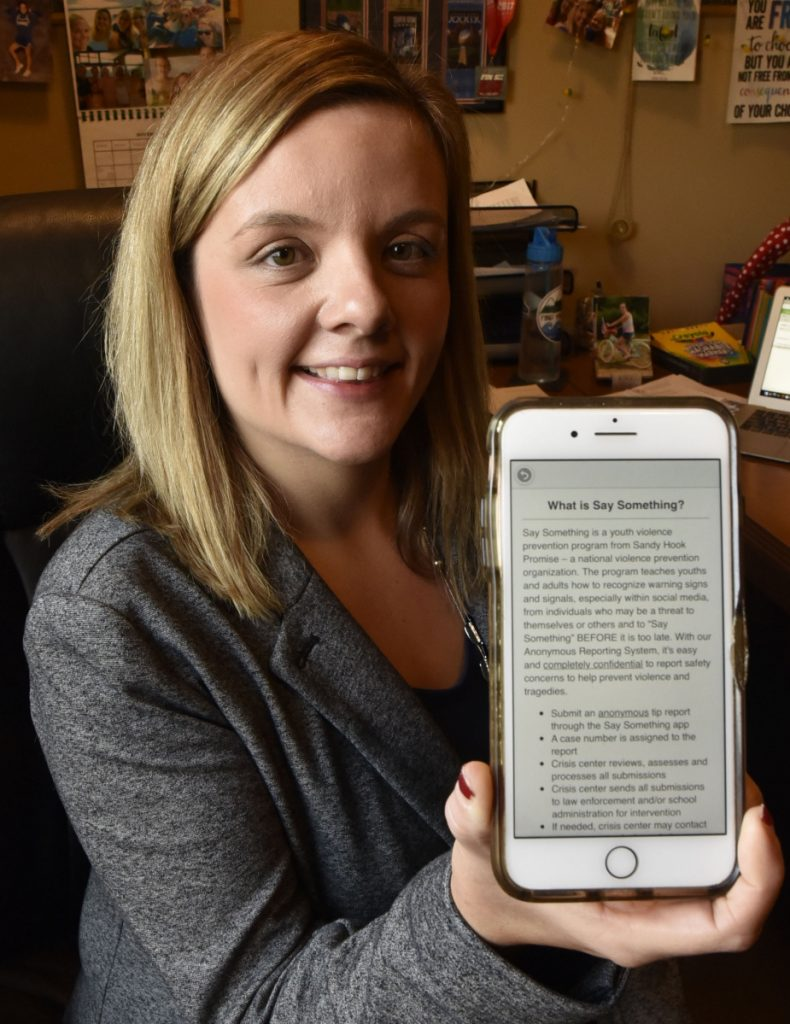 "Beth Carlton, student services coordinator at Mid-Maine Technical Center in Waterville, on Nov. 15, holds a cellphone with the ""Say Something"" app installed. Students will be offered the app to be used to notify officials if they hear or read inappropriate threats or comments."