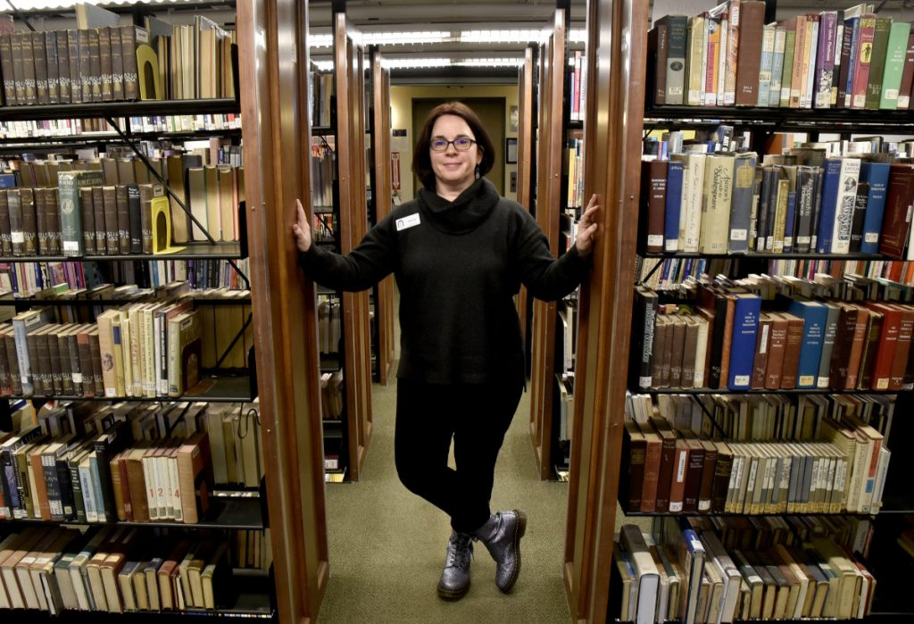 """Tammy Rabideau, the new director of the Waterville Public Library, in the main stack section of the library on Wednesday. The new director hopes to increasingly bring the Waterville and Colby communities together, choosing to refer to the area as one """"community with a capital C."""""""