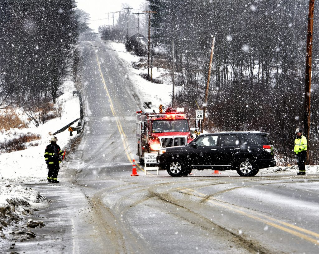 Firefighters from Madison detour traffic Sunday at the intersection of Route 43 and Molunkus Road in Cornville as police, working in falling snow, investigate a fatal accident on Route 43.