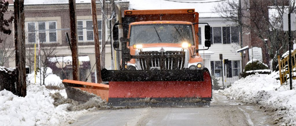 A Waterville Public Works department plow truck clears snow from city streets in Waterville during a snowstorm on Tuesday.