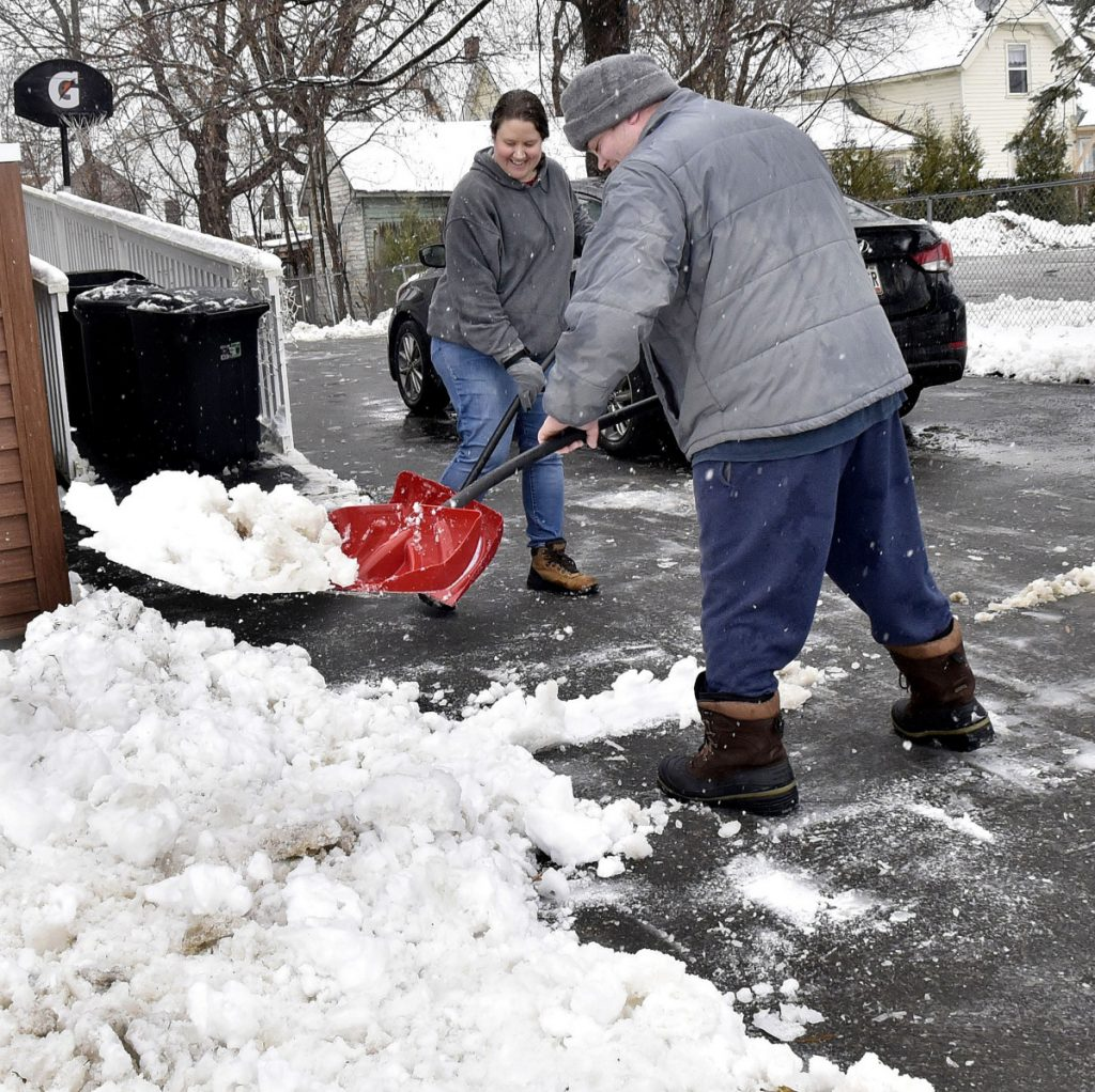 Amanda and William Carlton teamed up to shovel snow from driveway at their home in Waterville during a snowstorm on Tuesday.