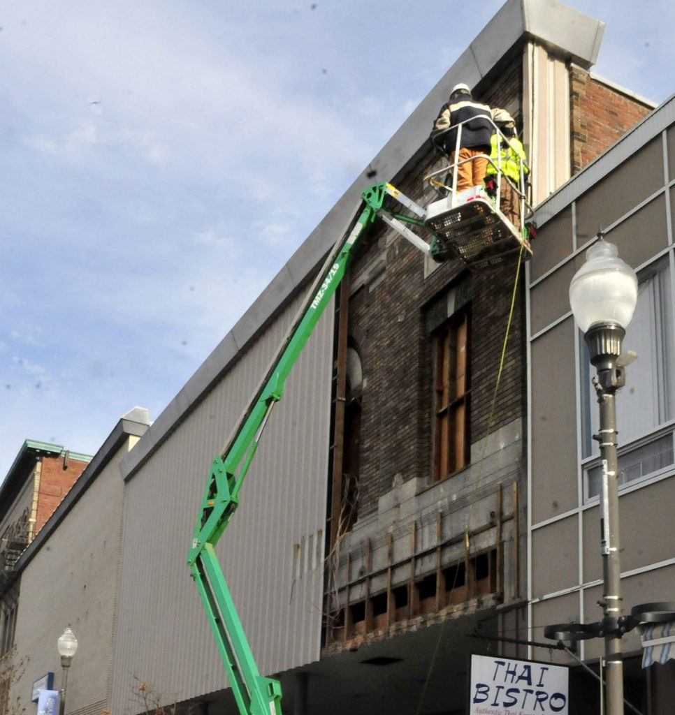 Workers remove the exterior facade covering the former Atkins building on Main Street in downtown Waterville in January. The Central Maine Growth Council is offering grants to make improvements to building facades in downtown Waterville.