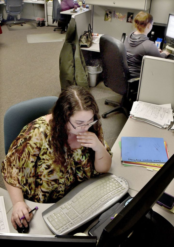 Brienna Pelletier, front, works on Thursday with other employees in the international audit department at the Parsifal Corp., which has moved its offices from Waterville to Eskelund Drive in Fairfield.