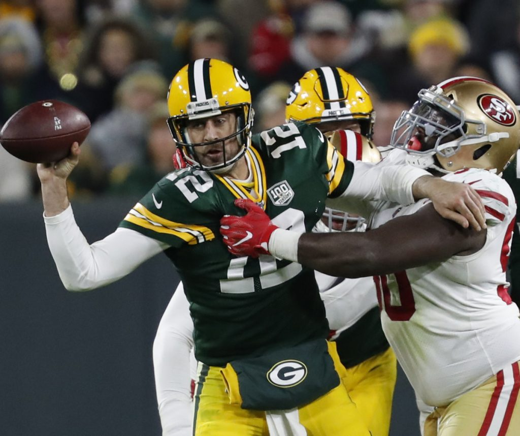 Green Bay Packers quarterback Aaron Rodgers (12) throws the ball away as he is tackled by San Francisco 49ers defensive tackle Earl Mitchell (90) during the second half of an NFL football game Monday, Oct. 15, 2018, in Green Bay, Wis. (AP Photo/Matt Ludtke)