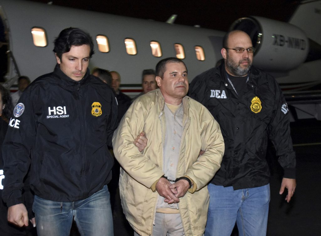 "Authorities escort Joaquin ""El Chapo"" Guzman from a plane in January 2017 at Long Island MacArthur Airport in Ronkonkoma, N.Y., after he was extradited from Mexico. His drug conspiracy trial begins Monday in New York City."