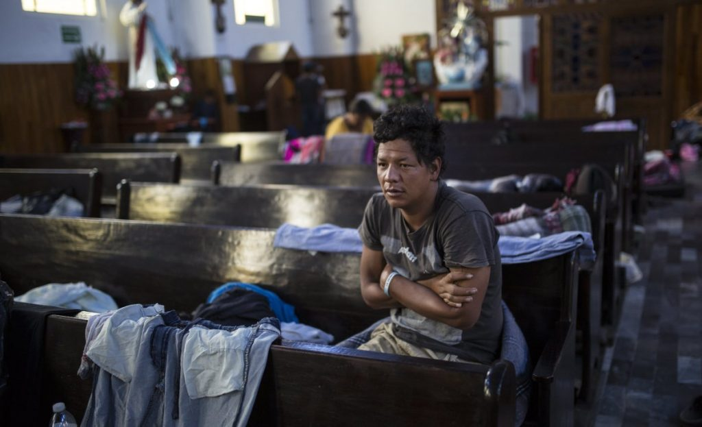 A Central American migrant wakes up Sunday in a church in Puebla, Mexico, that housed caravan members who separated from the main group.