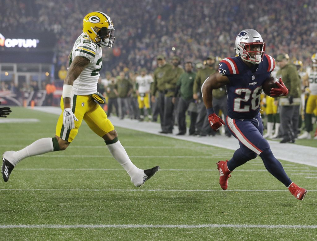 James White of the New England Patriots zips past Green Bay Packers cornerback Jaire Alexander for an 8-yard touchdown run Sunday night during the first quarter at Foxborough, Mass.