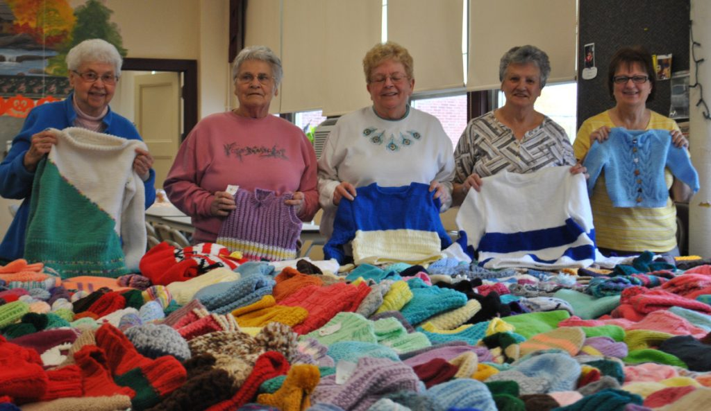 Knitting for Charity members, from left, Sister Theresa Couture, Paulette Ruel, Judy Kenny, Connie Vadnais and Louise Bosse display items the group has made at the J. Richard Martin Community Center in Biddeford on Monday.