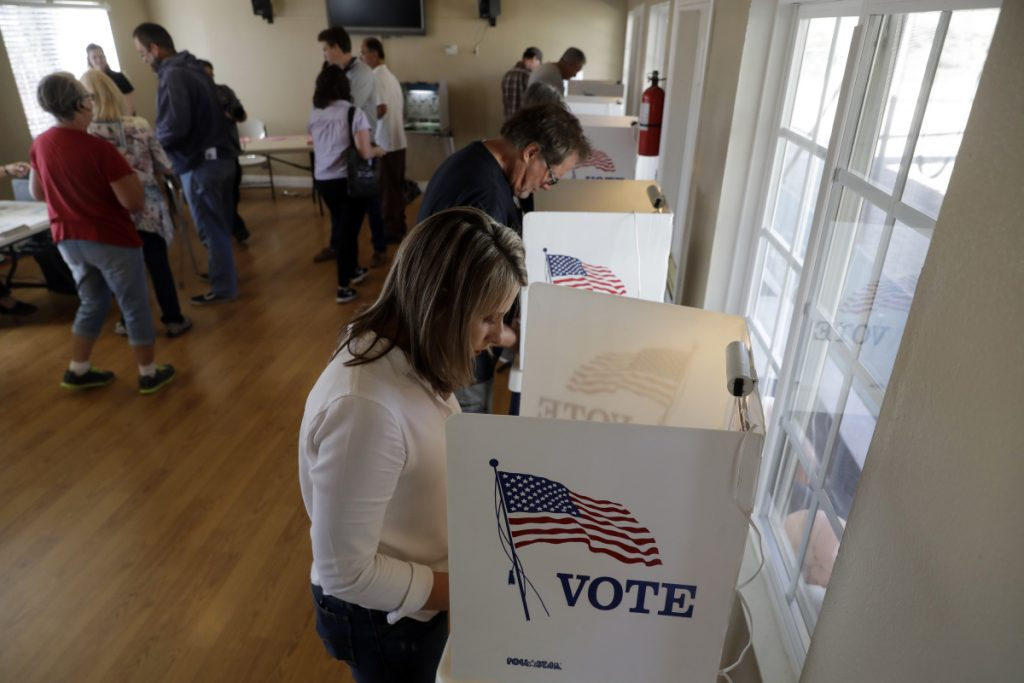 Katie Hill, bottom right, a Democratic Party candidate from California's 25th congressional district, votes Tuesday in Agua Dulce, Calif. Hill is running against Republican incumbent Steve Knight. The fight for control of the House could come down to a handful of seats, particularly in California.