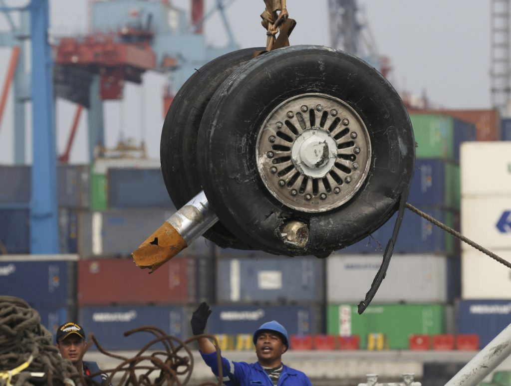 A crane moves two wheels recovered from the Lion Air jet that crashed into the Java Sea on Oct. 29 for further investigation in Jakarta, Indonesia.