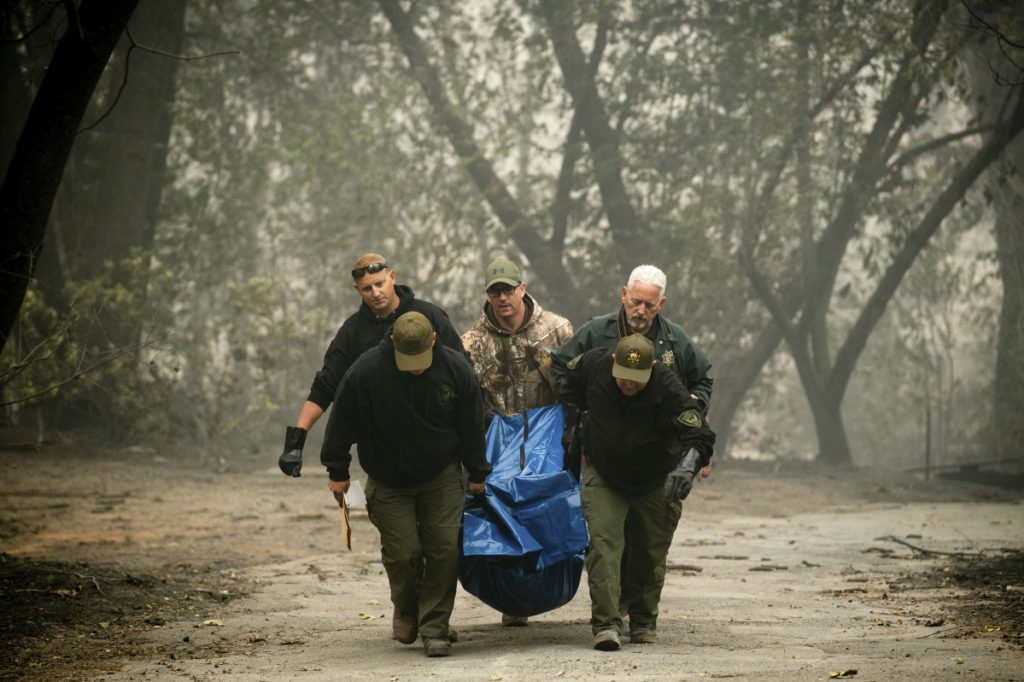 Sheriff's deputies recover the remains of a victim of the Camp Fire on Saturday in Paradise, Calif.
