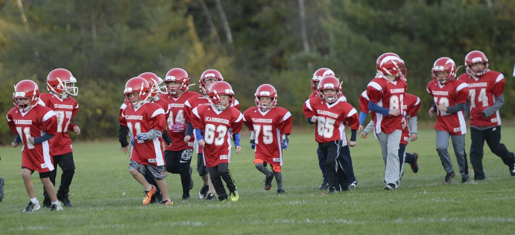 "Clinic participants warm up as they run a lap around the field during Scarborough's first ""Try Tackle"" football clinic in October."