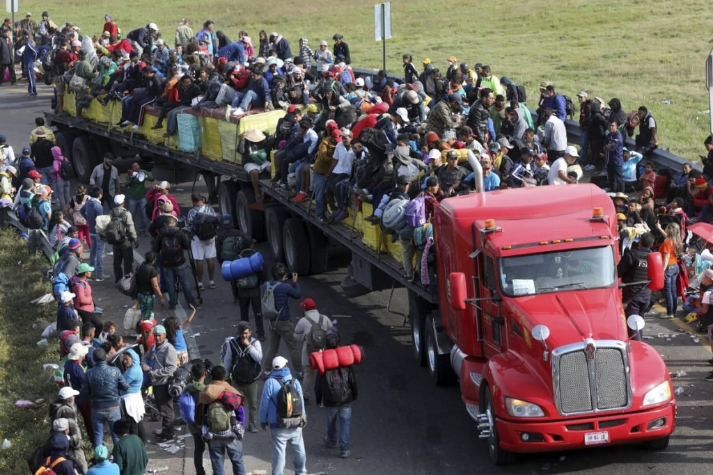Central American migrants, part of the caravan hoping to reach the U.S. border, get a ride on a eighteen wheeler pulling a trailer, in Irapuato, Mexico, Monday, Nov. 12, 2018. Several thousand Central American migrants marked a month on the road Monday as they hitched rides to the western Mexico city of Guadalajara and toward the U.S. border. (AP Photo/Rodrigo Abd)