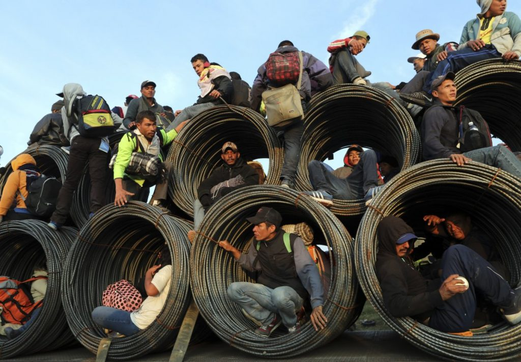 Central American migrants, part of the caravan hoping to reach the U.S. border, ride on a truck carrying rolls of steel rebar, in Irapuato, Mexico, on Monday. The migrants started out a month ago walking, but increasingly rely on getting rides.