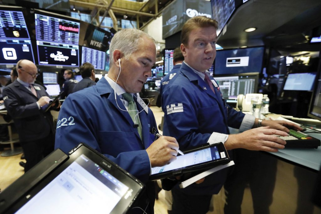 Timothy Nick, center, works with specialist Michael O'Mara on the floor of the New York Stock Exchange this month.