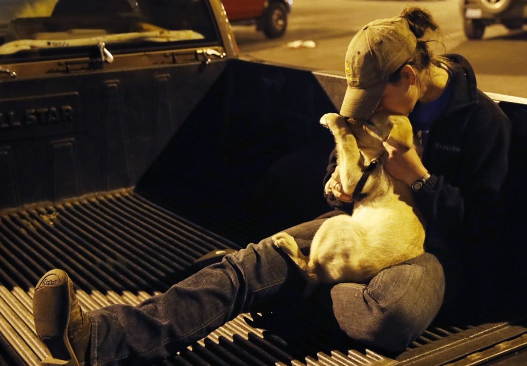 Sarah Gronseth kisses her dog Tuesday in Chico Calif. The teacher, who helped evacuate high school students, lost her Paradise home in the fire. Local governments should look at their decisions to allow subdivisions in places with high fire risks, an expert on building codes says.