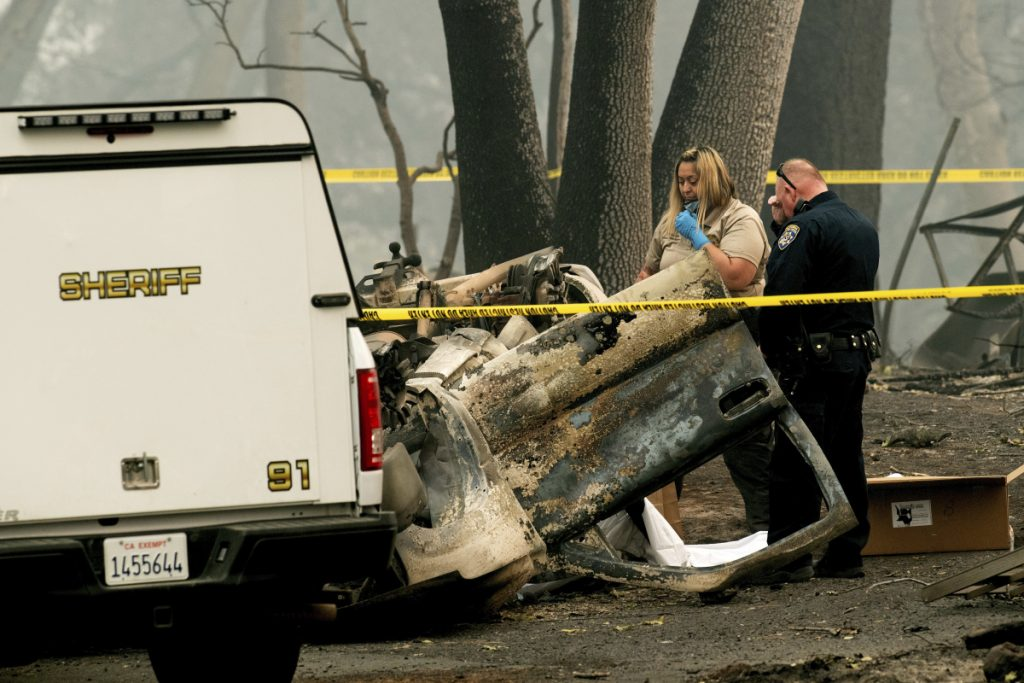 A sheriff's deputy recovers the remains of a Camp Fire victim from an overturned car in Paradise, California, on Thursday.