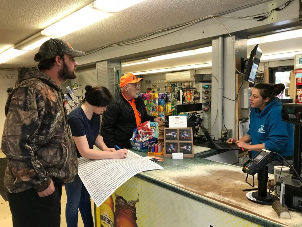 In West Gardiner, Four Corners General Store employees Dawn Hunt, right, and Jordan Shaw register Charles and Trevor Berry's deer in October. Maine has a much smaller herd than most Southern or Midwest states, with about 230,000 to 250,000 deer.