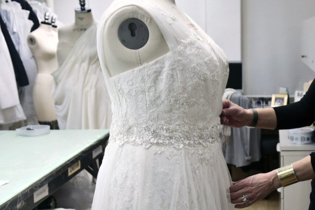 A David's Bridal employee arranges a dress on a mannequin in New York in this 2013 photo. David's Bridal is filing for bankruptcy protection but there is no danger for customers who have ordered dresses because operations will continue while the wedding and prom retailer restructures, the company says.