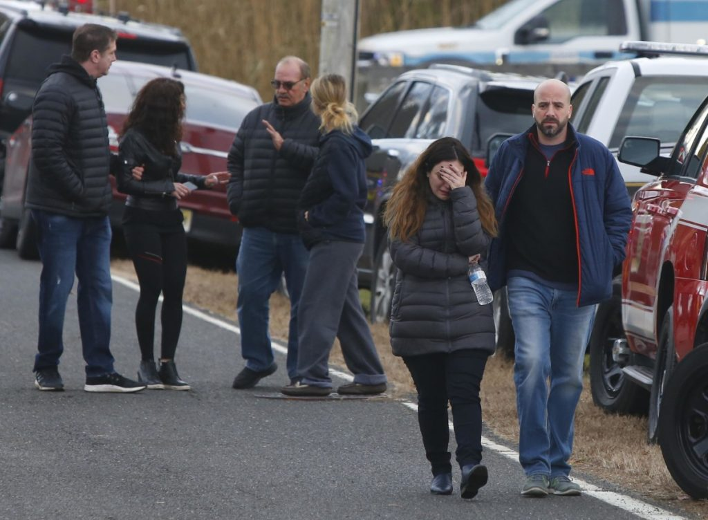 Pedestrians walk away from the scene of a fatal fire in Colts Neck, New Jersey, on Tuesday. Authorities say two adults and two children were found dead at the burning mansion near the New Jersey shore.