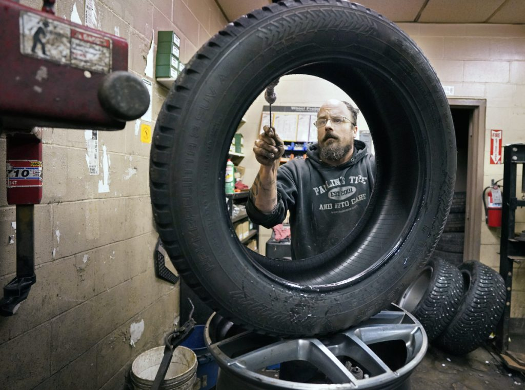 Greg Moreau, manager at Paulin's Tire & Auto Care in Portland, cleans off the bead of a studded snow tire that he is changing over for a customer Tuesday. Even with his two-man crew working 12-hour days, Moreau can squeeze in no more than 15 standard tire swaps a day between regular service appointments.
