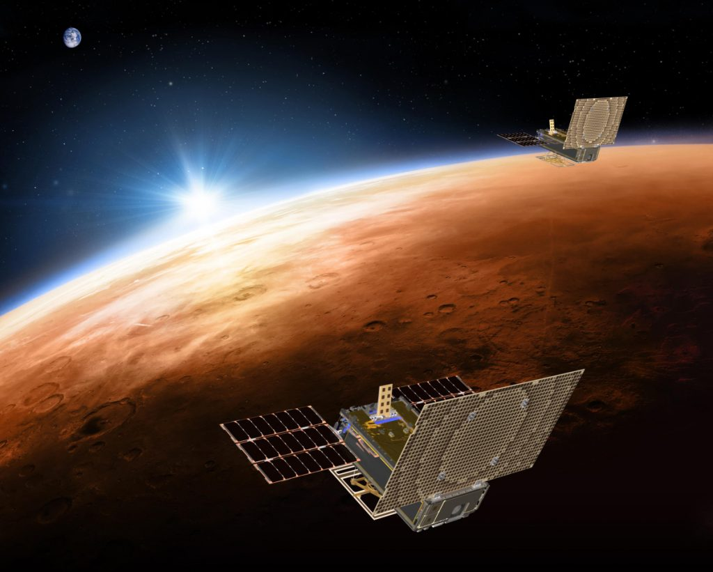 This illustration made available by NASA in March 2018 shows the twin Mars Cube One project, or MarCO, spacecrafts flying over Mars with Earth and the sun in the distance. The MarCOs will be the first CubeSats, a kind of modular, mini-satellite, flown into deep space.