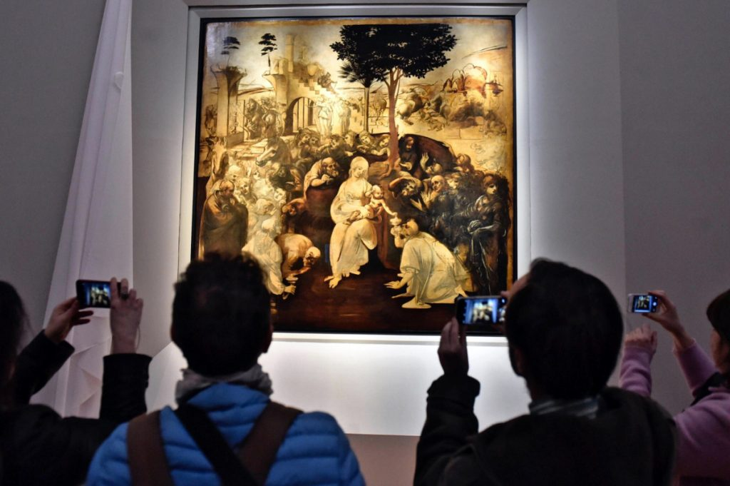 "Visitors take pictures of Leonardo da Vinci's ""Adoration of the Three Wise Men"" in the Uffizi museum in Florence, Italy. A 2017 arrangement to send Leonardo works to France for a blockbuster exhibit next year, the 500th anniversary of his death, has Italy's nationalist-leaning government up in arms."