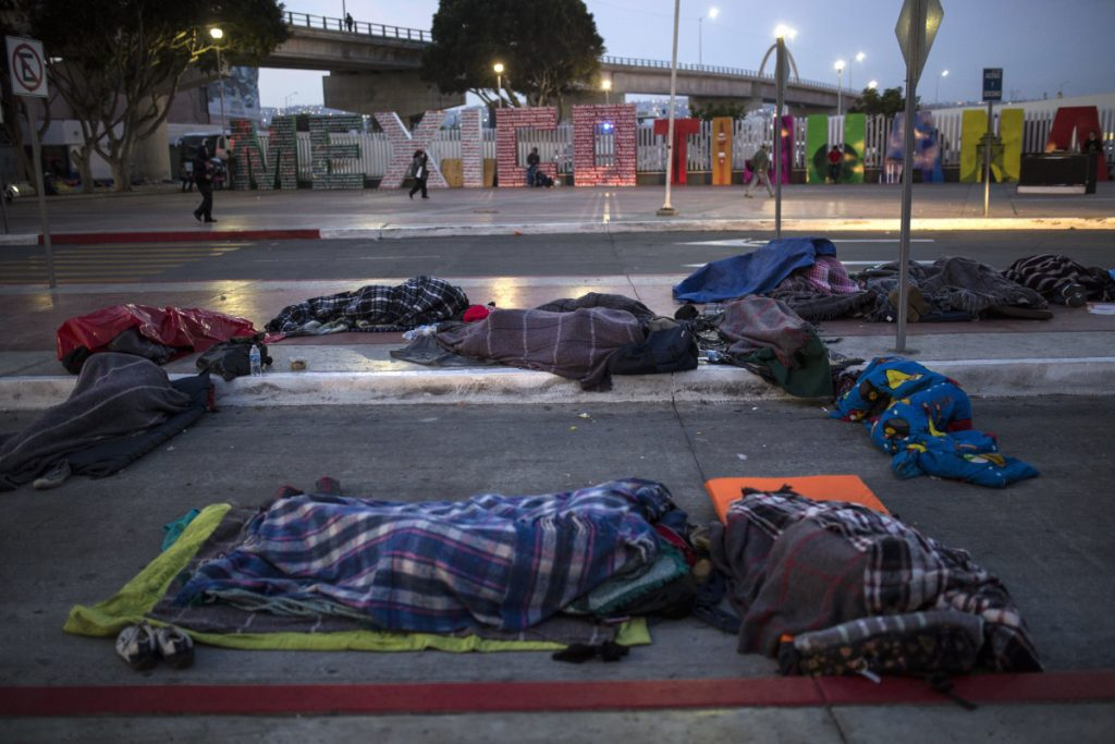 Migrants sleep on a street near the border crossing in Tijuana, Mexico, on Friday.