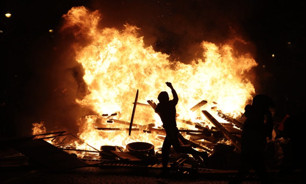 A demonstrator throws debris at a burning barricade Saturday while protesting fuel taxes in Paris.