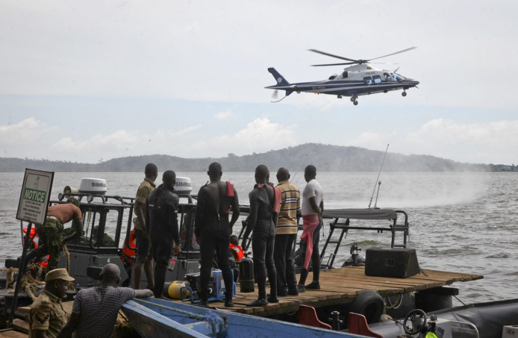 Ugandan divers look up as a helicopter searches for victims of a boat that capsized in Lake Victoria near Kampala, the capital of Uganda, on Sunday.