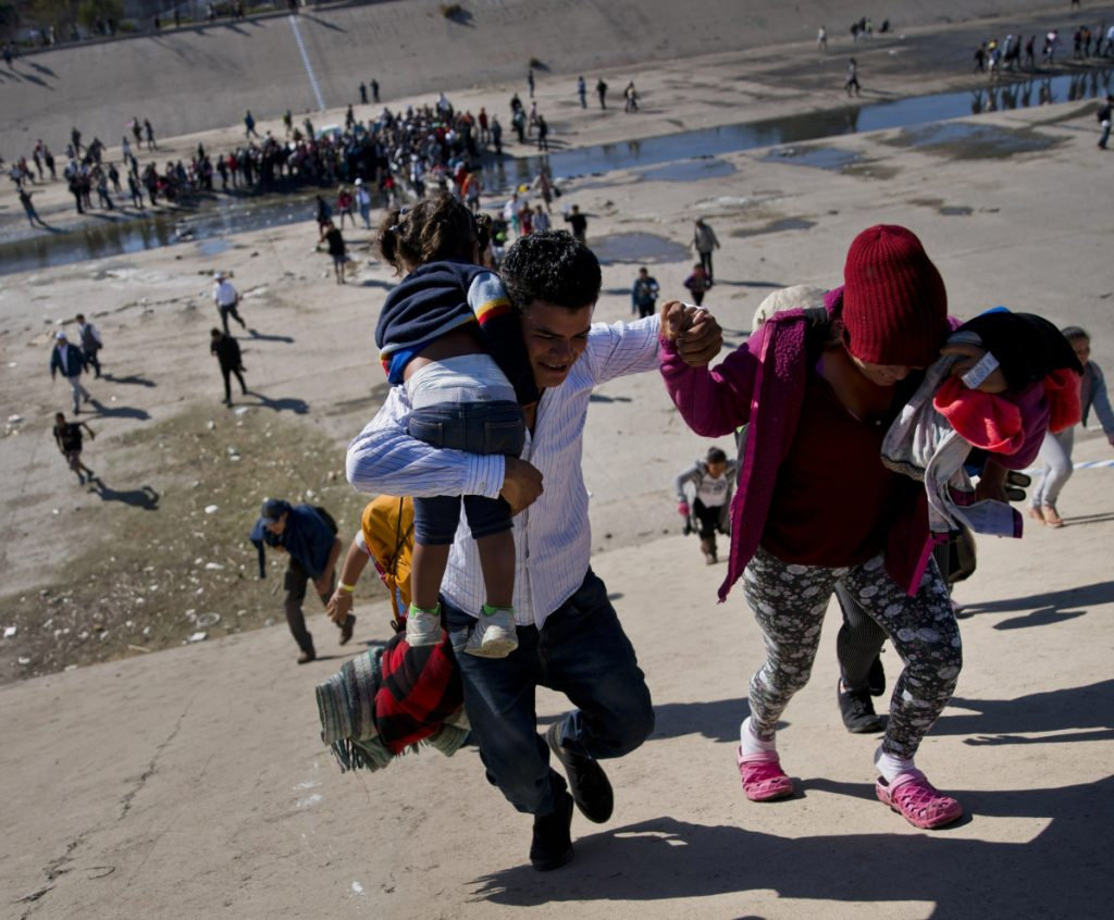 Migrants ascend a riverbank heading to the U.S. border after pushing past police in Tijuana, Mexico. Some who reached the fence were met with tear gas.