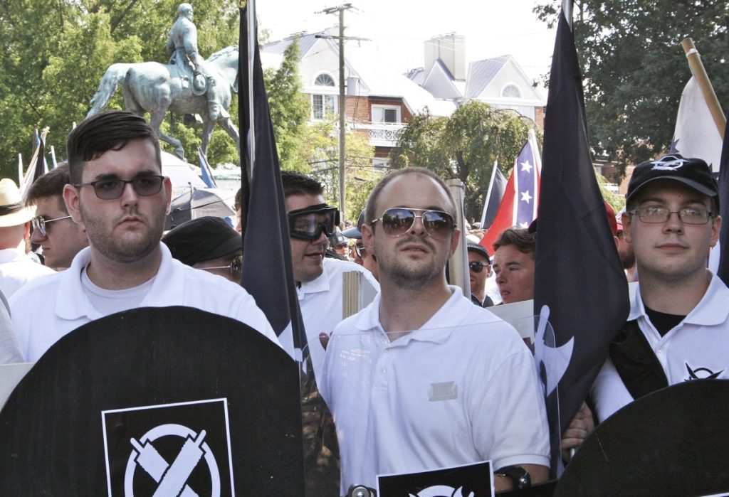 James Alex Fields Jr., left, holds a black shield in Charlottesville, Va., where a white supremacist rally took place. Fields Jr., of Maumee, Ohio, is charged with first-degree murder for allegedly driving his car into a crowd of people protesting against white nationalists.